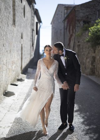 newlyweds-walk-through-italian-village-holding-hands-groom-kisses-bride-on-the-cheek