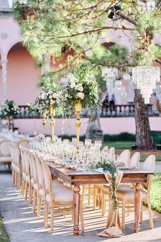 ringling-museum-wedding-reception-with-long-wooden-table-gold-centerpiece-stands