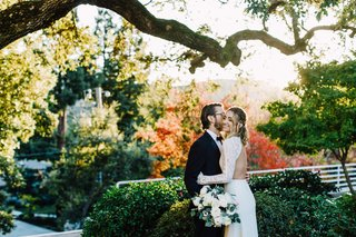 bride-in-backless-dress-with-lace-sleeves-groom-in-tuxedo-fall-foliage