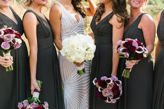 bride-in-naeem-khan-wedding-dress-holding-white-bouquet-and-bridesmaids-in-black-dresses-with-purple