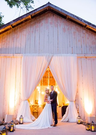 wedding-reception-in-rustic-chic-barn-bride-in-flower-crown-lanterns-leading-to-reception-space