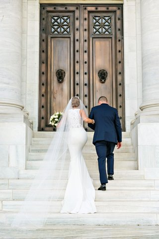 bride-in-form-fitting-wedding-dress-lace-back-bateau-neck-long-veil-cathedral-up-steps-washington-dc