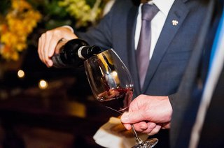 a-guest-pours-red-wine-for-another-guest-at-a-wedding-reception-in-a-wine-cellar