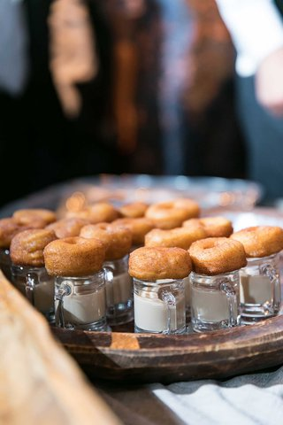 miniature-donuts-apple-cider-on-top-of-small-glass-mugs-with-milk-creme-cream-dip