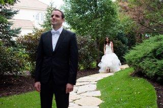 bride-in-monique-lhuillier-mermaid-wedding-dress-walks-up-to-groom-in-gibeon-tolbert-for-first-look