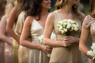 bridesmaids-in-mismatched-gold-dresses-bridesmaid-carrying-nosegay-of-white-roses