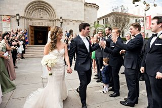 bride-in-ines-di-santo-wedding-dress-with-ivory-bouquet-holds-grooms-hand-after-wedding-ceremony