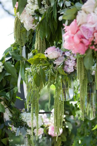 a-close-up-snapshot-of-a-couples-verdant-garden-arch-featuring-dripping-greenery-and-bright-flowers