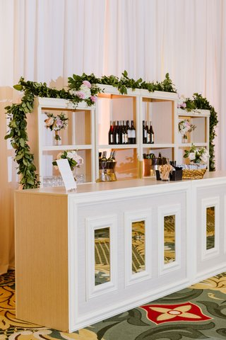 wedding-reception-ballroom-white-mirror-bar-with-shelves-garland-pink-blush-flowers-wine