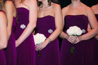 bridesmaids-in-strapless-purple-dresses-with-brooches-at-waist-holding-white-rose-bouquets