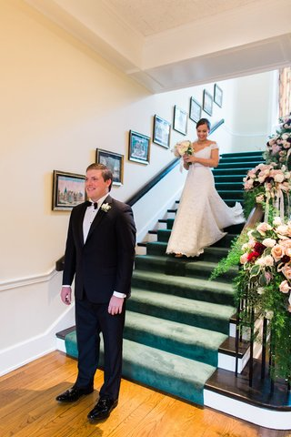 bride-in-legends-romona-keveza-lace-off-shoulder-wedding-dress-on-staircase-first-look-photo
