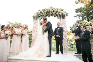 couple-kisses-after-exchanging-vows-under-floral-arch-at-ceremony