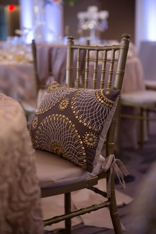 wedding-reception-with-chocolate-throw-pillow-with-beaded-pattern-on-gold-chiavari-chair