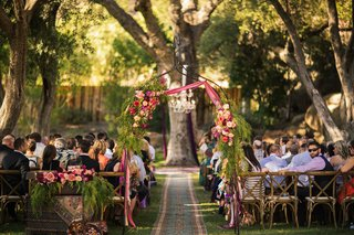 outdoor-bohemian-wedding-ceremony-in-tree-grove-with-metal-arch-peach-fuchsia-red-flowers-ribbons