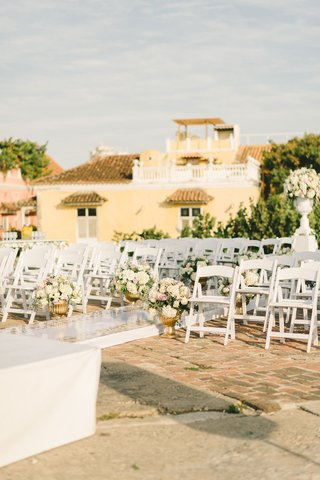 colombia-wedding-ceremony-raised-aisle-white-chairs-low-flowers-gold-urns