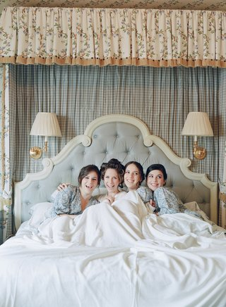 bride-in-hair-rollers-with-blue-robes-under-sheet-in-bed
