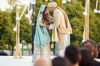 pakistani-couple-in-traditional-garb-of-white-blue-and-gold-exchanging-vows-in-front-of-guests