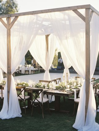 outdoor-wedding-reception-with-wooden-structure-and-soft-white-drapery