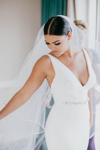 bride-in-v-neck-wedding-dress-jewel-belt-sash-middle-part-sleek-coiffure-low-bun-pretty-makeup-lash