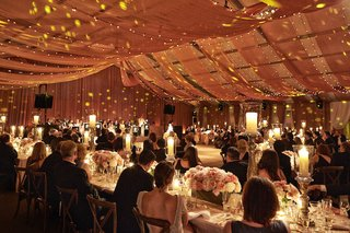 guests-sitting-at-reception-tables-with-drapes-overhead