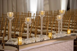 gold-and-crystal-votive-candles-along-aisle-on-mirror-stand