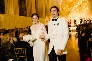bride-in-white-illusion-lace-long-sleeve-dress-groom-in-white-tuxedo-jacket-gold-backdrop-texas-nye