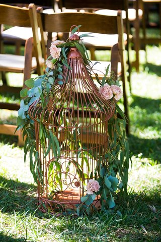 a-large-copper-lantern-lining-the-aisle-featuring-winding-green-foliage-and-blush-flowers