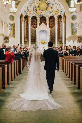 wedding-ceremony-at-church-in-miami-guests-taking-photos-on-their-camera-phones-bride-walking-down