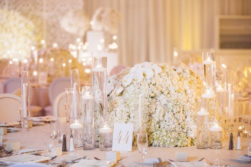 wedding reception low centerpiece white hydrangea and orchid flower arrangement