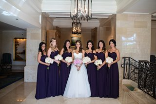 bride-wearing-ball-gown-with-bridesmaids-in-eggplant-dresses