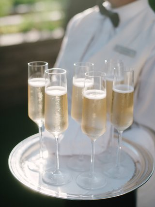 wedding-outdoor-cocktail-hour-server-with-tray-of-full-champagne-glasses