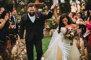 stephanie-perez-and-brandon-hampton-walking-up-aisle-bride-in-detachable-train-overskirt