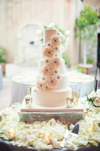 wedding-cake-surrounded-by-white-flower-petals-and-sugar-flower-decorations-mercury-glass-candles