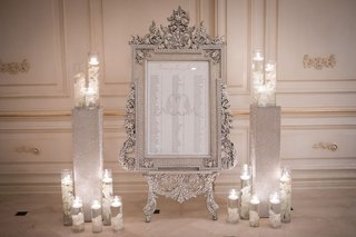 ashley-alexiss-wedding-reception-seating-chart-in-ornate-silver-frame-floating-candles-white-flowers