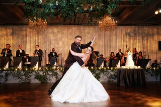 bride-in-ball-gown-wedding-dress-with-groom-in-burgundy-suit-dip-during-first-dance-live-band
