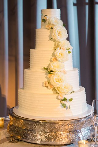 5-tier-cake-with-white-frosting-and-white-roses-and-green-leaves-curving-down-cake