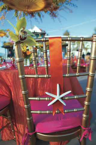 gold-chair-with-pink-cushion-and-orange-ribbon-decorated-with-starfish