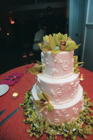 white-cake-covered-with-green-orchids-on-top-and-bottom