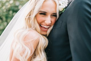 bride-smiling-large-smile-while-hugging-groom-long-blonde-hair-veil-groom-boutonniere