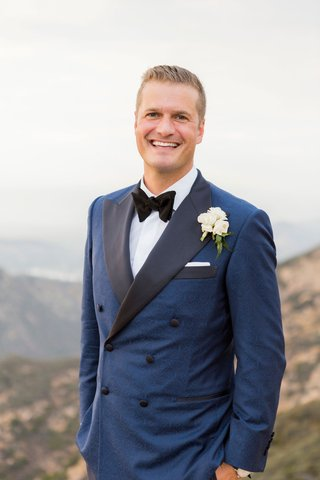 groom-in-tuxedo-navy-double-breasted-tuxedo-jacket-black-lapel-bow-tie-pocket-square