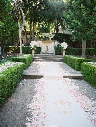 outdoor-ceremony-space-at-estate-with-white-aisle-runner-white-pink-petals-logo-with-couple-name