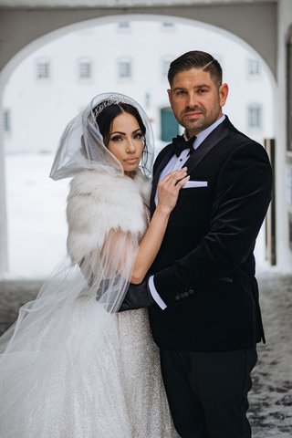 bride-in-sparkle-wedding-dress-with-fur-wrap-and-hood-cape-groom-with-black-gloves-and-tuxedo-snow