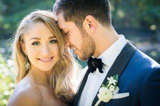 groom-in-navy-tuxedo-black-lapel-bow-tie-white-ranunculus-boutonniere-stephanotis-blossom