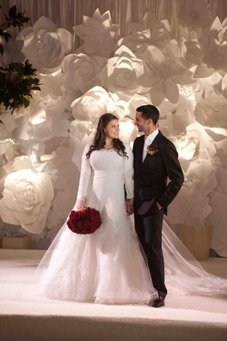 bride-in-long-sleeve-wedding-dress-with-groom-and-red-bouquet