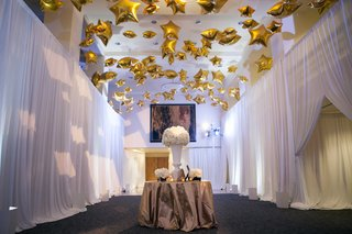 gold-star-shaped-balloons-on-ceiling-at-cocktail-hour-for-new-years-eve-wedding-above-table-drapery