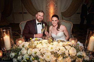 white-flowers-and-greenery-at-sweetheart-table-chicago-wedding-maroon-tuxedo-for-groom-strapless