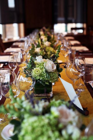 green-and-white-flower-arrangements-on-wood-table