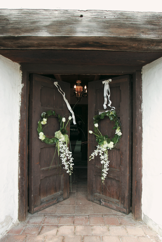 church-doors-decorated-with-white-ribbons-and-green-wreaths-with-white-flowers
