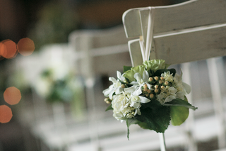 wedding-ceremony-seats-decorated-with-bundles-of-green-and-white-flowers