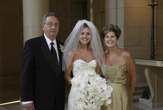 bride-standing-in-front-of-venue-with-parents